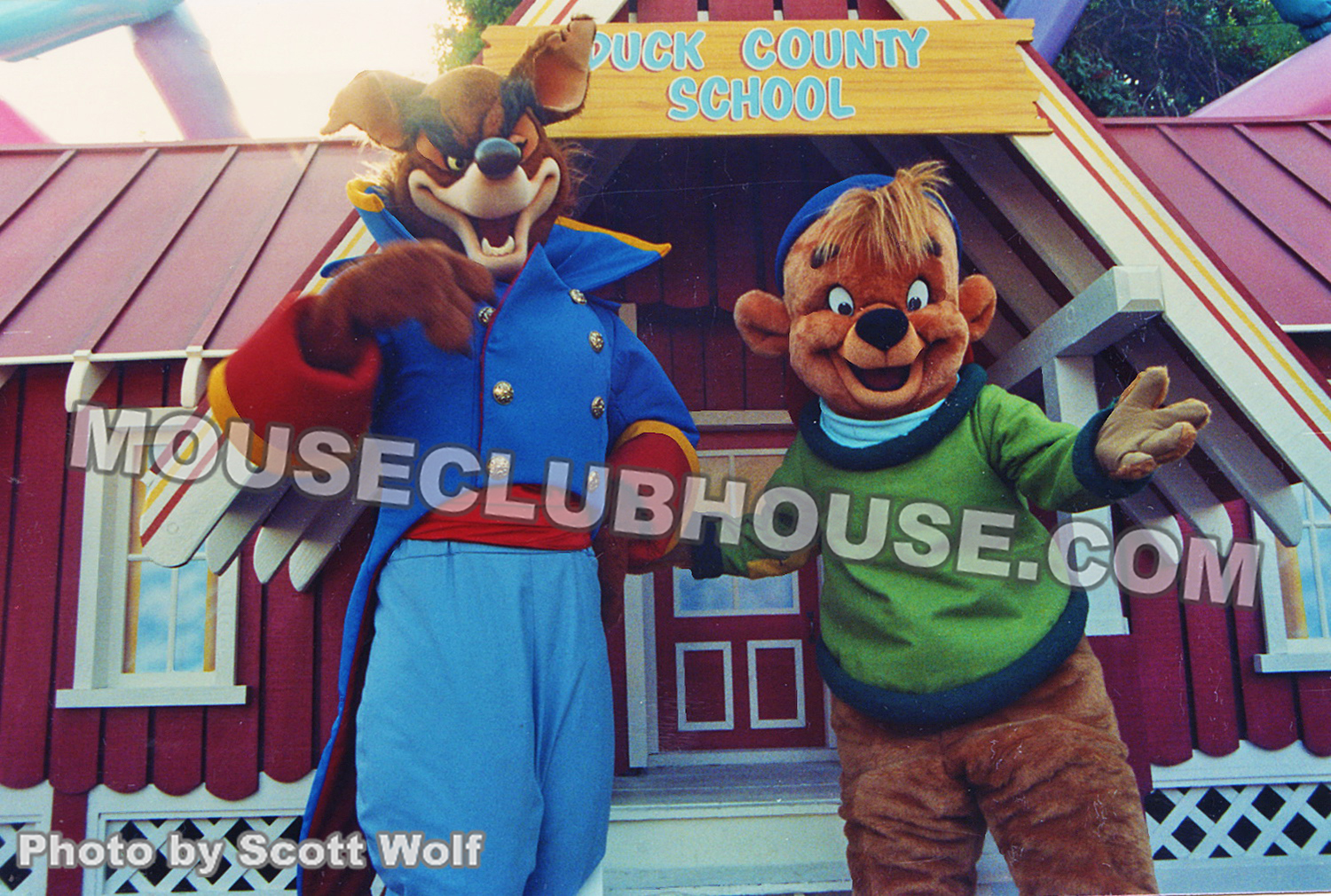 Mixing up shows, characters from TaleSpin pose in front of the DuckTales school in Disneyland